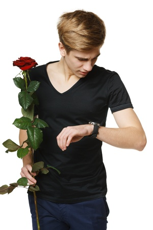 courtship: Young hansome man holding red rose and looking at his wirstwatch controlling time, over white background Stock Photo