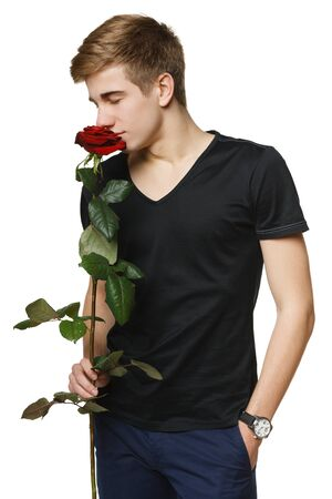 Young handsome man smelling the red rose with closed eyes, over white background photo