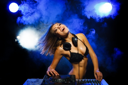 dj: Excited DJ girl on decks on the party Stock Photo
