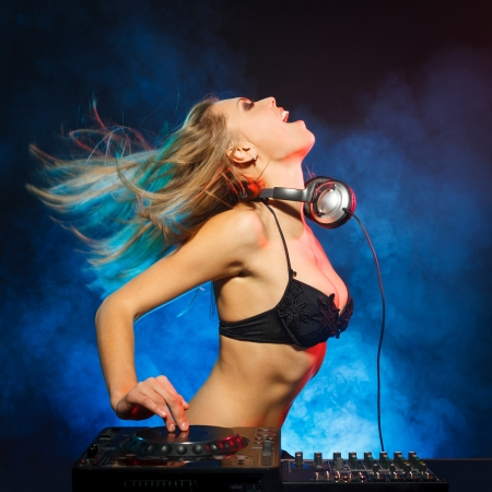 auriculares dj: Emocionado chica DJ en cubiertas en el partido Foto de archivo