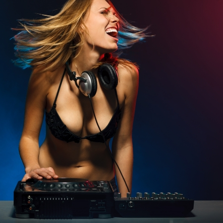Excited DJ girl on decks on the party photo