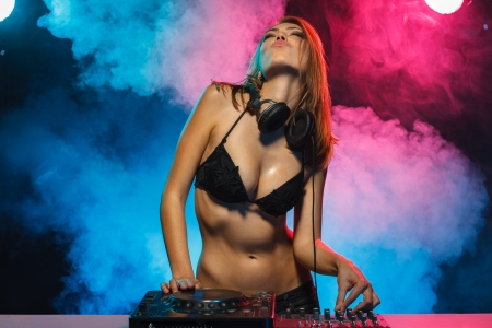 deejay: Excited DJ girl on decks on the party Stock Photo