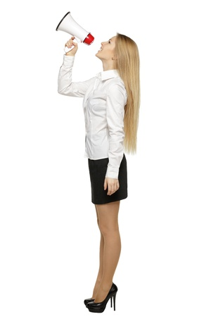 Side view full length of young business woman with megaphone, over white background photo