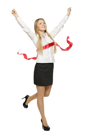 Full length of beautiful businesswoman crossing the finishing line, over white background