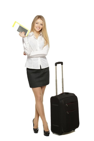 Full length portrait of young business woman standing with her travel bag, holding the tickets with passport, isolated on white background photo