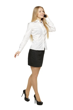 Full length of businesswoman walking talking on mobile phone, isolated on white background photo