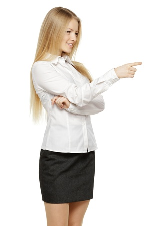 Beautiful blond business woman pointing at copy space over white background photo