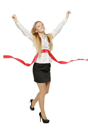 Full length of beautiful businesswoman crossing the finishing line, over white background photo