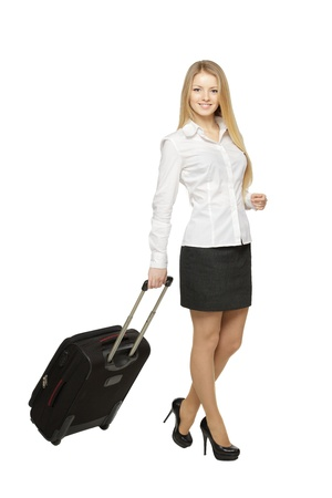Full length of young business woman pulling the travel bag, isolated on white background photo