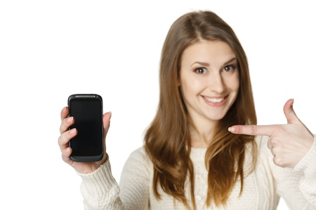 holding cell: Closeup of happy young woman pointing at her mobile phone  Shallow depth of field, focus at the cell phone  Stock Photo