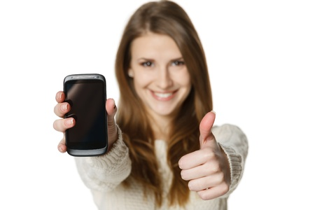 Closeup of happy young woman showing her mobile phone and gesturing thumb up sign  Shallow depth of field, focus at the cell phone