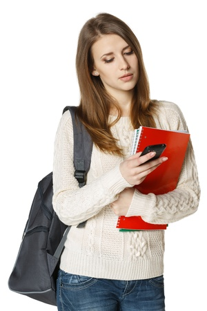 university text: Woman university student with backpack and books sending a sms on cell phone, isolated on white background