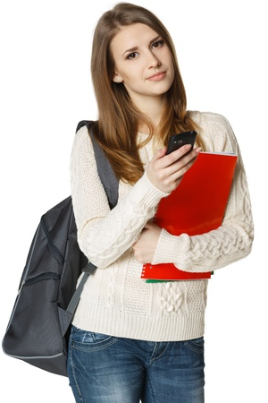Woman university student with backpack and books sending a sms on cell phone, isolated on white background