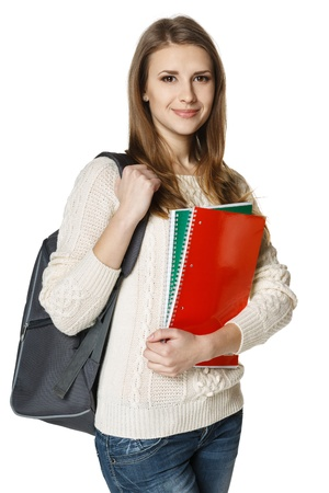 Young woman wearing a backpack and holding botebooks ready to go to class, over white background