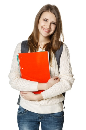 Happy young woman wearing a backpack and holding notebooks ready to go to class, over white background photo