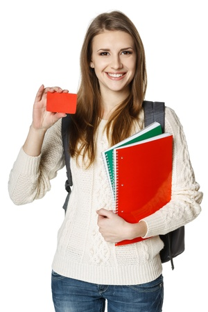 Happy young woman wearing a backpack and holding notebooks showing blank credit card, over white background  Student loan concept  photo