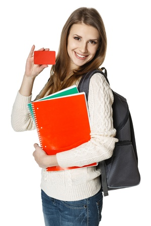 woman credit card: Happy young woman wearing a backpack and holding notebooks showing blank credit card, over white background  Student loan concept  Stock Photo