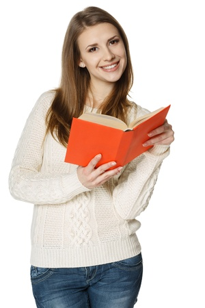 Happy smiling woman student standing with opened book, over white background photo