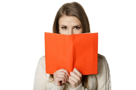 library student: Closeup of young woman peeking over the edge of the opened book, looking at camera, over white background