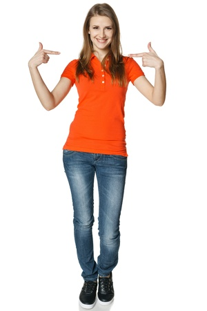 face centered: Young casual woman pointing at herself cheering happy standing in full length, isolated on white background Stock Photo