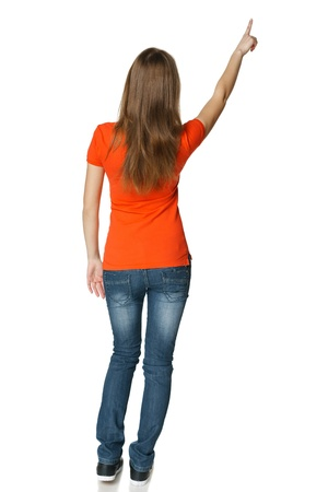 Back view of young casual female in full length pointing at blank copy space, isolated on white photo
