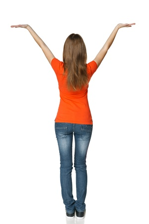 back up: Back view of young casual female in full length holding blank copy space, isolated on white