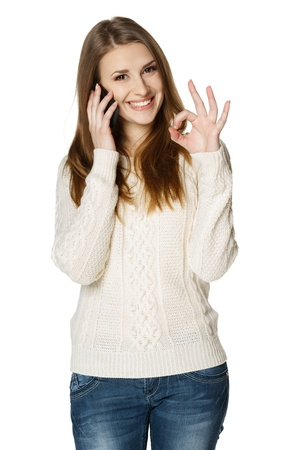 Happy woman talking on cell phone and showing OK sign, over white background