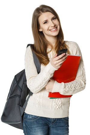 Happy woman university student with backpack and books sending a sms on cell phone, isolated on white background