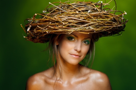 Closeup of beautiful young woman with fresh makeup and wicker nest on her head over green background photo