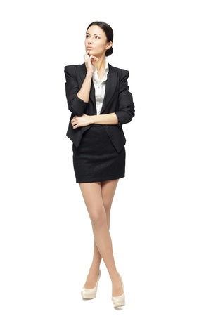 cross armed: Business woman standing in full length looking upwards isolated on white background