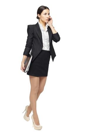Full length of businesswoman walking talking on mobile phone, isolatedon white background photo