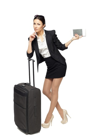 Full-body portrait of young business woman standing with black travel bag and holding the tickets with passport isolated on white background photo