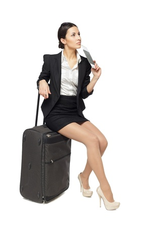 Full-body portrait of young business woman sitting on her black travel bag and holding the tickets with passport isolated on white background Stock Photo - 18303481