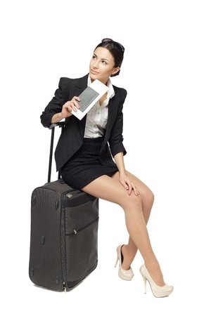 sideways: Full-body portrait of young business woman sitting on her black travel bag and holding the tickets with passport isolated on white background