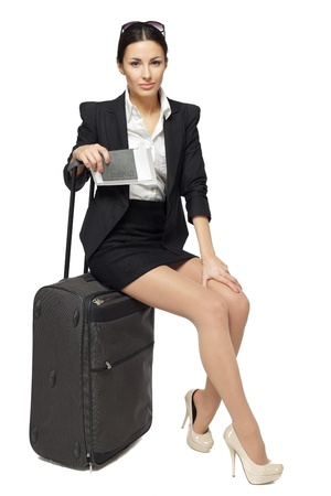 Full-body portrait of young business woman sitting on her black travel bag and holding the tickets with passport isolated on white background photo