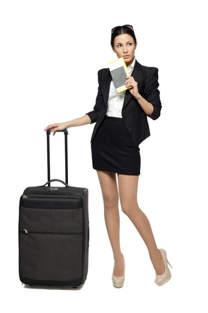 Full length portrait of young business woman standing with her travel bag, holding the tickets with passport, looking sideways at blank copy space, isolated on white background photo