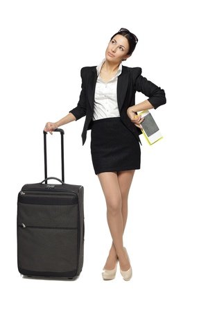 aside: Full length portrait of young business woman standing with her travel bag, holding the tickets with passport, looking sideways at blank copy space, isolated on white background Stock Photo