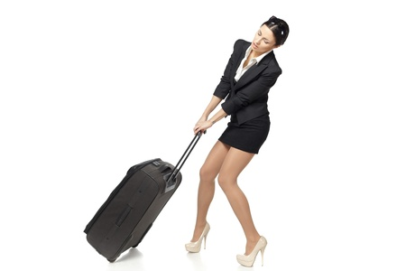 Full length of young business woman pulling the heavy travel bag, isolated on white background photo