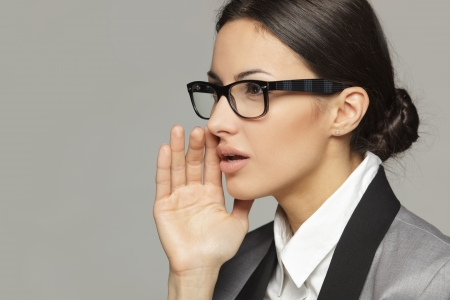 whisper: Side view portrait of business woman  calling out to someone over grey background Stock Photo