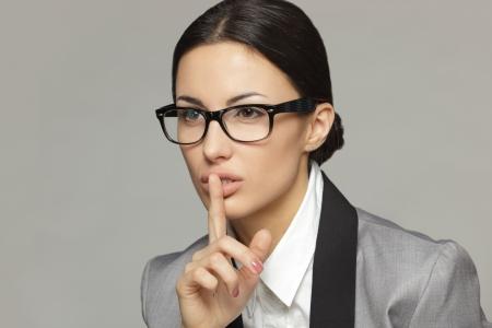 quiet adult: Primo piano di donna d'affari con il dito sulle labbra su sfondo grigio