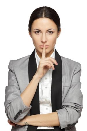 Femme d'affaires avec le doigt sur les lèvres sur fond gris Banque d'images