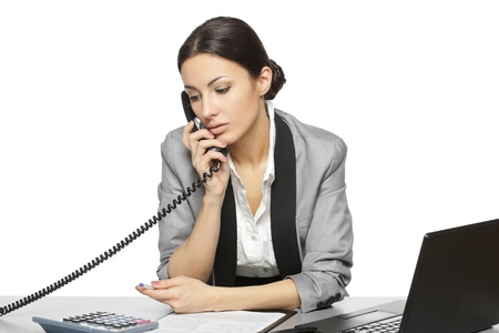 at her desk: Serious business woman looking at laptop screen while talking on the phone at her work desk, isolated on white background