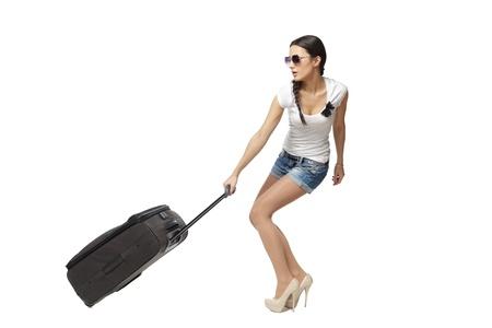 Full length of young woman in casual pulling the heavy travel bag, isolated on white background photo