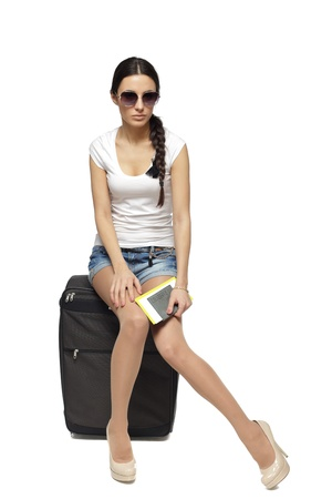 Full  length of young female in casual sitting on her black travel bag and holding the tickets with passport isolated on white background photo