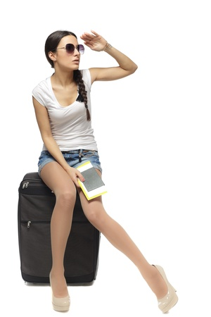 sideways: Full length of young woman sitting on her travel bag and holding the tickets with passport looking faraway isolated on white background