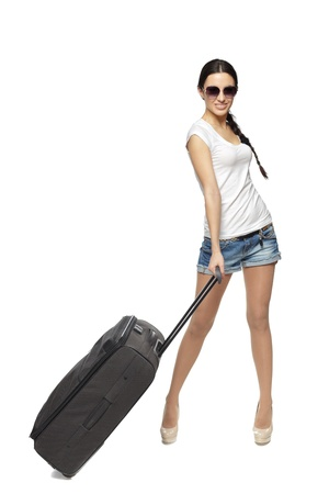 Full length of young female standing with the travel bag, isolated on white background photo