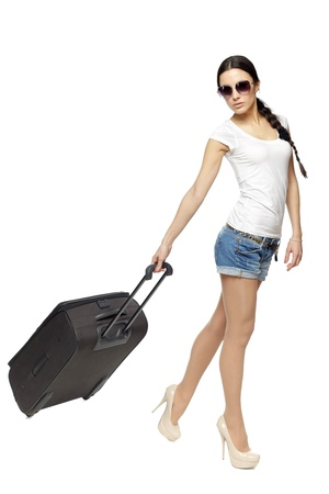 Full length of young female in casual pulling the travel bag, isolated on white background photo