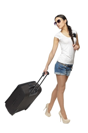 Full length of young female pulling the travel bag, isolated on white background photo