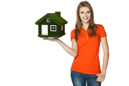 Happy casual female showing eco house, isolated over a white background photo