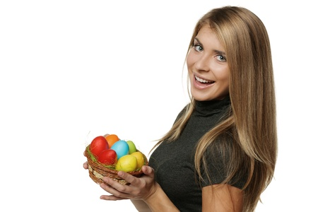 Smiling woman holding basket with Easter eggs, isolated on white background